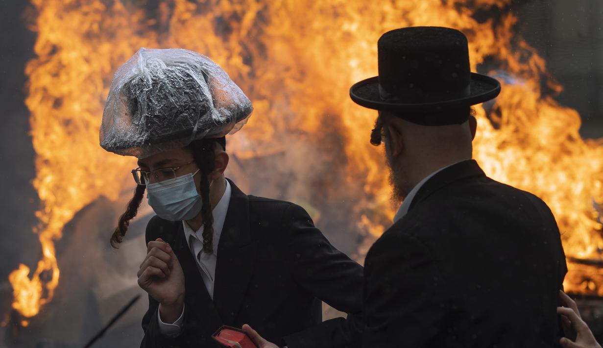 Pria Yahudi Ultra-Ortodoks memakai masker saat membakar beragi sebagai persiapan akhir untuk liburan Paskah di kota Yahudi ultra-Ortodoks Bnei Brak, dekat Tel Aviv, Israel (26/3/2021).  Dalam perayaan ini umat Yahudi dilarang memakan makanan beragi seperti roti tawar. (AP Photo/Oded Balilty)