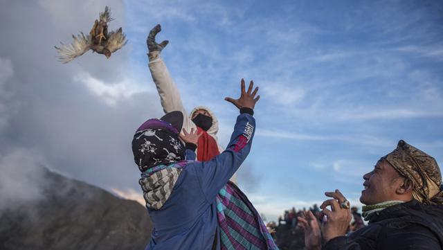 Suku Tengger melarung sesajen ke kawah Gunung Bromo saat upacara Yadnya Kasada di Probolinggo, Jawa Timur, Sabtu (26/6/2021). Suku Tengger mempersembahkan sesajen berupa beras, buah, ternak, dan barang lainnya untuk mencari berkah dari dewa. (Juni Kriswanto/AFP)
