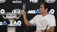 Juara Australia Terbuka 2018 Roger Federer mengajak bersulang pada konferensi pers usai mengalahkan Marin Cilic di final, Minggu (28/1/2018). (AP Photo/Vincent Thian)