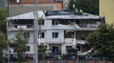 Sejumlah petugas menutupi kantor polisi dengan kain di Istanbul usai dibom, Senin (10/8/2015). Sebuah truk bermuatan bahan peledak membombardir kantor polisi yang melukai tiga anggota dan tujuh warga sipil. (REUTERS/Huseyin Aldemir)