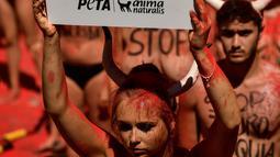Seorang Aktivis berunjuk rasa memprotes adu banteng dalam Festival San Fermin di depan Balai Kota di Pamplona, Spanyol utara, (5/7). Festival ini melibatkan banyak orang dalam pertunjukan adu banteng, musik dan tarian. (AP Photo/Alvaro Barrientos)