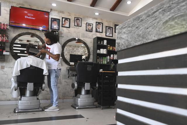 Dalam gambar pada 8 April 2021, tukang cukur Pakistan Ali Abbas menggunakan pisau daging untuk memotong rambut seorang pelanggan di tokonya di Lahore. Berharap membuktikan kemampuannya dalam persaingan, Ali Abbas mengandalkan berbagai alat yang tidak biasa untuk melatih keahliannya. (Arif ALI/AFP)