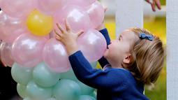 Putri Charlotte memegang balon saat menghadiri pesta anak-anak di Government House, Kanada, (29/9). Tingkah lucu putra dan putri pasangan Pangeran William dan Kate Middleton menjadi perhatian orang yang datang ke pesta tersebut. (REUTERS/Chris Wattie)