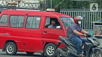 Supir angkot sedang melintas di kawasan Raya Bogor, Jakarta, Jumat (5/2/2021). Di tengah lonjakan kasus COVID-19 masih banyak masyarakat yang abai terhadap protokol kesehatan. (Liputan6.com/Herman Zakharia)