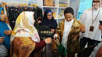 Menteri BUMN Rini M Soemarno melihat produk UMKM dari Rumah Kreatif BUMN (RKB) binaan BNI saat Launching Halal Park di Senayan Jakarta, Selasa (16/4). Presiden Joko Widodo (Jokowi) resmi membuka miniatur arena bertajuk Moslem District Destination tersebut. (Liputan6.com/Angga Yuniar)
