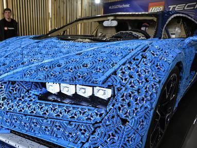 Pengunjung mengamati replika mobil Bugatti Chiron dari jutaan balok Lego Technic pada sebuah pameran di Taman Gorky Moskow, Selasa (23/7/2019). Mobil berwarna biru tersebut dibuat menggunakan lebih dari 1 juta blok Lego Technic dengan berat totalnya sekitar 1.500 kg. (Alexander NEMENOV/AFP)