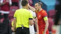 Striker Wales, Gareth Bale (kanan) melakukan protes kepada wasit usai kebobolan gol kedua saat melawan Denmark dalam laga babak 16 Besar Euro 2020 di Johan Cruiyff ArenA, Amsterdam, Sabtu (26/6/2021) malam WIB. (Foto: AP/Pool/Peter Dejong)