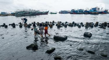 Anak-anak bermain di pesisir laut Jakarta, Kamis (9/1/2020). Pemprov DKI Jakarta melalui Dinas Sumber Daya Air (SDA) memetakan kawasan yang rawan diterjang banjir rob selama cuaca ekstrem melanda Jakarta pada 9 hingga 12 Januari 2020. (merdeka.com/Imam Buhori)