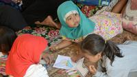 Anak-anak pengungsi korban gempa belajar di tenda pengungsian di Lapangan Tanjung, Lombok Utara, Rabu (8/8). Lebih dari 70.000 orang kehilangan tempat tinggal akibat gempa Lombok berkekuatan 7 SR yang melanda pada Minggu (5/8). (AFP/SONNY TUMBELAKA)