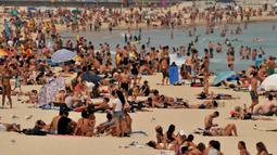 Pengunjung berjemur di pantai Bondi ketika pantai Bondi ketika suhu udara melonjak di Sydney (21/12/2019). Australia terganggu akibat bencana ganda yakni gelombang panas dan kebakaran hutan serta lahan di kawasan tersebut. (AFP/Farooq Khan)