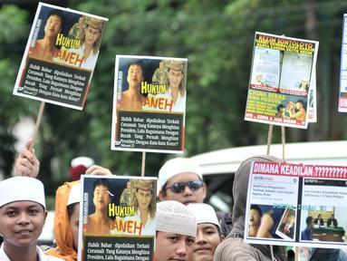 Massa Laskar Pembela Islam (LPI) saat mengawal pemeriksaan Habib Bahar bin Smith di depan Gedung Bareskrim Polri, Jakarta, Kamis (6/12). Massa membawa sejumlah poster tuntutan saat aksi. (Merdeka.com/Iqbal Nugroho)