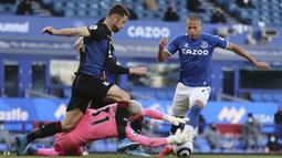 Kiper Crystal Palace, Vicente Guaita (tengah) berhasil menangkap bola dari ancaman striker Everton, Richarlison dalam laga lanjutan Liga Inggris 2020/2021 pekan ke-30 di Goodison Park, Liverpool, Senin (5/4/2021). Crystal Palace bermain imbang 1-1 dengan Everton. (AP/Clive Brunskill/Pool)
