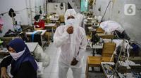 Pekerja memakai pakaian untuk Alat Pelindung Diri (APD) tenaga medis di kawasan Penggilingan, Jakarta, Kamis (26/3/2020). Harga yang dijual untuk APD bekisar antara Rp 45.000 untuk jenis pakaian sekali pakai dan Rp 75.000 untuk pakaian yang bisa dicuci. (Liputan6.com/Faizal Fanani)