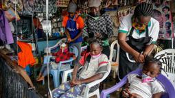 Tiga orang anak rambutnya ditata dengan model yang terinsprasi dari corona Covid-19 oleh Mama Brayo Beauty Salon di daerah kumuh Kibera, Kenya, 3 Mei 2020. Corona telah menghidupkan kembali gaya rambut di Afrika Timur yang memiliki lonjakan kepang bentuk khas virus. (AP/Brian Inganga, File)