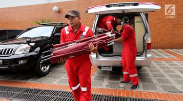 Petugas Airport Rescue & Fire Fighting Officer menurunkan tandu lipat di Gedung VIP Terminal 1B, Bandara Internasional Soekarno-Hatta, Tangerang, Senin (29/10). Sebanyak 20 tandu lipat digunakan untuk pengambilan antemortem. (Liputan6.com/Fery Pradolo)