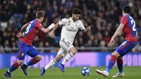 Gelandang Real Madrid, Marco Asensio, berusaha melewati gelandang CSKA Moskow, Ivan Oblyakov, pada laga Liga Champions di Stadion Santiago Bernabeu, Madrid, Rabu (12/12). Madrid kalah 0-3 dari CSKA. (AFP/Javier Soriano)