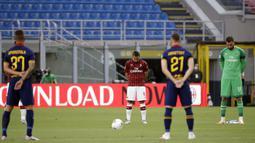 Para pemain AC Milan dan AS Roma mengheningkan cipta sebelum bertanding pada pertandingan Serie A di Stadion San Siro, Milan, Minggu (28/6/2020). AC Milan naik ke posisi 7 klasemen dengan 42 poin usai mengalahkan AS Roma 2-0. (AP Photo/Luca Bruno)