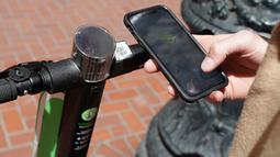Seorang pria bernama Jack Handlery menggunakan aplikasi di ponsel pintarnya untuk menggunakan skuter bermotor di San Francisco (17/4). (AP/Jeff Chiu)