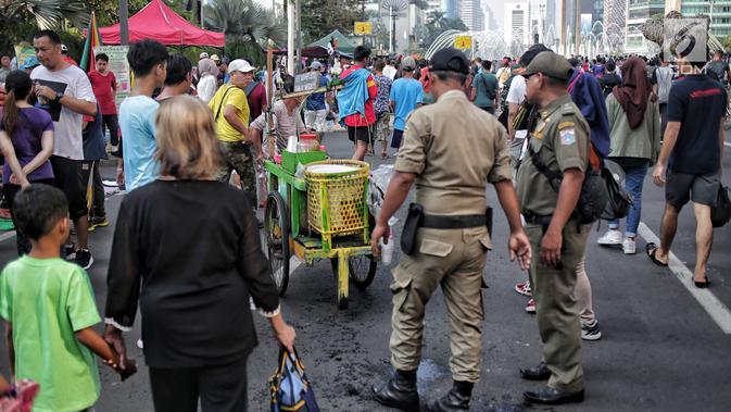 Petugas Satpol PP menertibkan PKL yang berdagang di kawasan Car Free Day, Bundaran HI, Jakarta, Minggu (5/5/2019). Kurangnya pengawasan menyebabkan banyak PKL berjualan tidak pada tempat yang telah di sediakan Pemprov DKI sehingga mengganggu aktivitas warga berolahraga. (/Faizal Fanani)