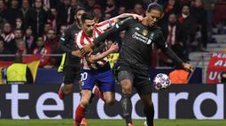 Bek Liverpool, Virgil van Dijk, berebut bola dengan gelandang Atletico Madrid, Vitolo, pada leg pertama 16 besar Liga Champions di Stadion Wanda Metropolitano, Madrid, Rabu (19/2) dini hari WIB. Atletico menang 1-0 atas Liverpool. (AFP/Pierre Philippe Marcou)