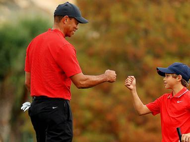Maestro golf Tiger Woods tampak begitu dekat dengan anaknya yang bernama Charlie Axel Woods. (Mike Ehrmann/Getty Images/AFP)