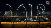 Coretan lampu tahun 2018 menghiasi malam pergantian tahun baru di kawasan silang Moumen Nasional (Monas), Jakarta, Senin (1/1/2018). (Liputan6.com/Johan Tallo)