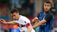 Pemain Inter Milan,  Rafinha berebut bola dengan pemain Cagliari, Andrea Cossu pada laga pekan ke-33 Serie A, di Giuseppe Meazza, Selasa (17/4).  Menjamu Cagliari, Inter Milan memetik kemenangan meyakinkan dengan skor 4-0. (AP/Antonio Calanni)