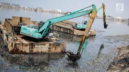 Eskavator dan tongkang Dinas Tata Air DKI Jakarta mengeruk lumpur dan sampah dari Waduk Pluit, Jakarta, Selasa (11/12). Pengerukan ini juga untuk mencegah pertumbuhan eceng gondok yang mengakibatkan pendangkalan Waduk Pluit. (Liputan6.com/Faizal Fanani)