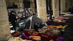 Orang-orang beristirahat di kasur saat mereka menempati gereja Saint-Jean-Baptiste-au-Beguinage di Brussels, Belgia, Selasa (2/2/2021). Beberapa ratus imigran tanpa surat-surat resmi, dengan izin pastor, telah menduduki gereja sejak Minggu, 31 Januari 2021 lalu. (AP Photo/Francisco Seco)