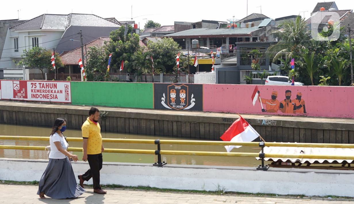 Warga berjalan di depan mural bertema Kemerdekaan RI pada dinding turap Sungai Ciliwung di kawasan Kampung Melayu, Jakarta, Minggu (16/8/2020). Mural karya petugas Pekerja Penanganan Sarana dan Prasarana Umum (PPSU) itu dibuat dalam rangka memeriahkan HUT ke-75 RI. (Liputan6.com/Immanuel Antonius)