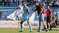Pelatih Persela Lamongan, Nilmaizar, tengah memberikan instruksi kepada kapten Persela, Eky Taufik, dalam sebuah pertandingan Liga 1 2019. (Bola.com/Aditya Wany)