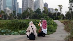 Warga menyalurkan hobi fotografi di area Hutan Kota Gelora Bung Karno, Jakarta, Kamis (20/6/2019). Sore hari banyak warga memanfaat waktu luang dengan berolahraga dan menyalurkan hobi fotografi di area Hutan Kota Gelora Bung Karno. (Liputan6.com/Helmi Fithriansyah)