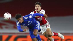 Pemain Leicester City, James Justin, berebut bola dengan bek Arsenal, Hector Bellerin, pada laga Liga Inggris di Stadion Emirates, Minggu (25/10/2020). Arsenal tumbang dengan skor 0-1. (Catherine Ivill/Pool via AP)
