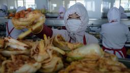 Dalam foto pada 1 Desember 2020, pekerja menyortir kubis di lini produksi pembuatan kimchi di Pabrik Kimchi Ryugyong di Pyongyang, Korea Utara. Setiap tahunnya, pabrik itu menghasilkan sekitar 4.200 ton acar khas Korea yang terbuat dari sayuran kubis yang diawetkan tersebut. (KIM Won Jin/AFP)