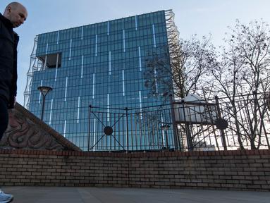 Pejalan kaki melintas dekat gedung baru kedutaan Amerika Serikat (AS) di Embassy Gardens, London, Inggris, Senin (18/12). Gedung itu disebut-sebut sebagai kantor kedutaan termahal dan tercanggih dengan dilengkapi sistem keamanan tinggi (Justin TALLIS/AFP)