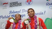 Dua atlet angkat besi Indonesia, Sri Wahyuni Agustiani dan Eko Yuli Irawan menunjukkan medali perak di Terminal 2 di Bandara Soetta, Minggu (14/08). Pemerintah menjanjikan bonus sebesar Rp 2 miliar untuk peraih medali perak. (Liputan6.com/Helmi Afandi)