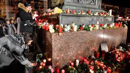 Warga meletakkan lilin dan bunga saat berkabung untuk para korban penembakan brutal di Hanau, Jerman, Kamis (20/2/2020). Warga menyalakan lilin dan membawa mawar berkumpul dalam diam. (AP Photo/Martin Meissner)