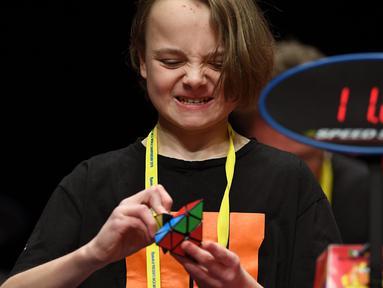 Seorang anak semangat memecahkan permainan rubik pada kejuaraan kubus Rubik Dunia di Melbourne, Australia (12/7/2019). Kejuaraan Dunia diadakan setiap dua tahun dan telah menarik 905 pesaing dari seluruh dunia yang bersaing dalam 18 acara yang berbeda. (AFP Photo/William West)