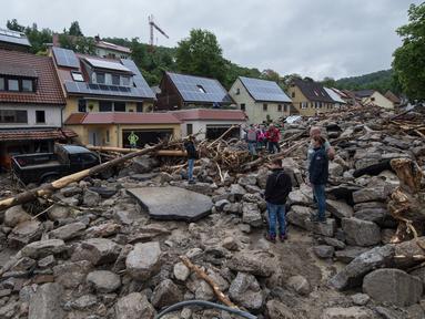 Warga mengamati jalan rusak menyusul bencana banjir dahsyat di Braunsbach, Senin (30/5). Empat orang tewas dan beberapa luka-luka akibat banjir melanda wilayah barat Jerman setelah hujan deras terjadi sepanjang Ahad (29/5). (Marijan Murat/dpa/AFP)