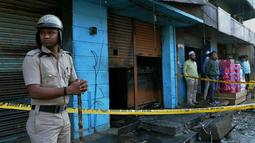Seorang polisi berjaga di depan restoran yang terbakar di Bangalore, India (8/1). Polisi mengatakan sebuah arus listrik pendek yang menyebabkan kebakaran di Kailash Bar & Restoran di pusat teknologi selatan Bangalore. (AFP Photo/Manjunath Kiran)
