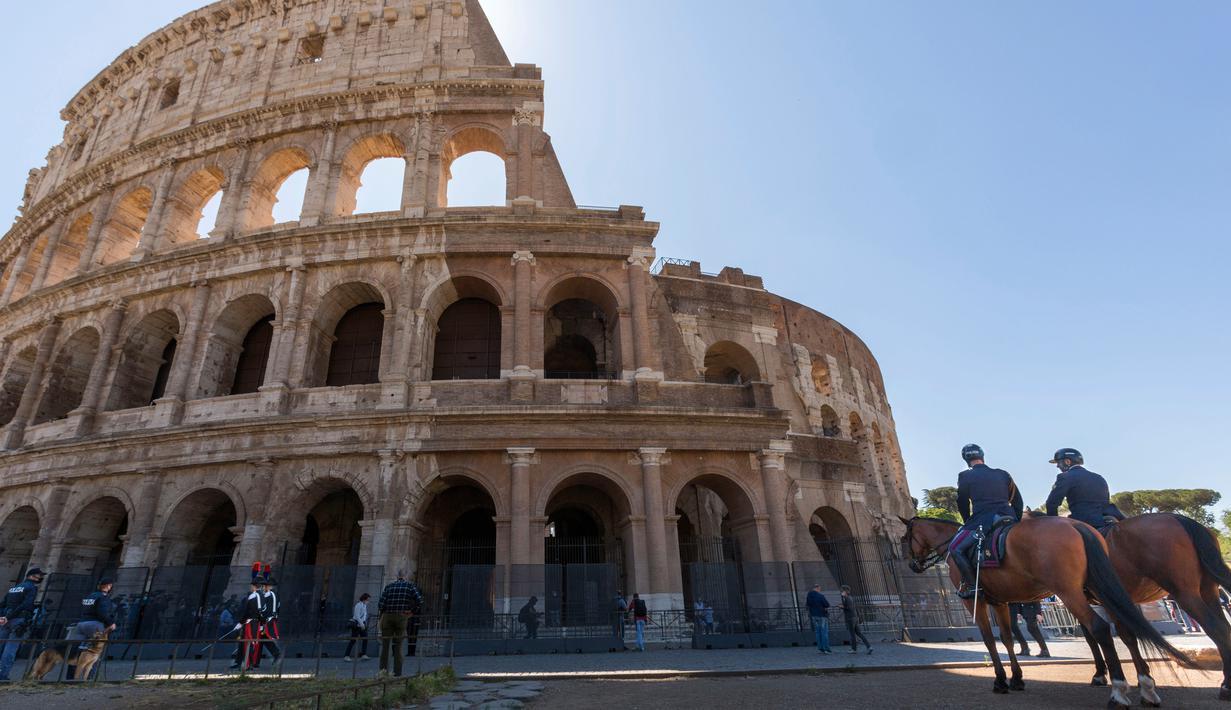 Polisi (kanan) dan petugas Carabinieri berpatroli di luar Colosseum di Roma, Italia, Senin (1/6/2020). Colosseum, yang merupakan ikon kota Roma dibuka kembali untuk umum pada Senin (1/6), setelah ditutup lebih dari dua bulan, dengan beberapa pembatasan akses bagi pengunjung. (AP/Domenico Stinellis)
