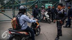 Mahasiswa melintas di gerbang pintu masuk Universitas Trisakti, Grogol, Jakarta, Rabu (24/8). Sebelumnya, sekitar 30 orang dari pihak Yayasan Trisakti tiba dan langsung masuk untuk mengeluarkan pihak pengamanan rektor lama. (Liputan6.com/Faizal Fanani)