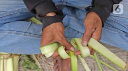 Pedagang menyelesaikan pembuatan kulit ketupat di kawasan Cibubur, Jakarta, Rabu (30/7/2020). Pedagang musiman menjelang Idul Adha tersebut menjual kulit ketupat dengan harga Rp 10 ribu, sedangkan ketupat yang siap untuk dihidangkan seharga Rp 30 ribu. (Liputan6.com/Herman Zakharia)