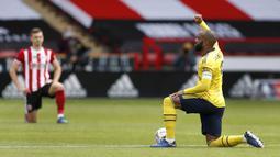 Pemain Arsenal Alexandre Lacazette (kanan) mengacungkan kepalan tangannya saat berlutut sebelum pertandingan menghadapi Sheffield United pada putaran keenam Piala FA di Bramall Lane, Sheffield, Inggris, Minggu (28/6/2020). Arsenal menaklukkan Sheffield United 2-1. (Andrew Boyers/Pool via AP)