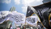 Aktivis Perempuan HTI mengibarkan bendera HTI saat melakukan aksi di Bundaran HI, Jakarta, Minggu (22/3/2015). Mereka menolak sistem neoliberalisme dan neoimperialisme yang digunakan oleh Indonesia.(Liputan6.com/Faizal Fanani)