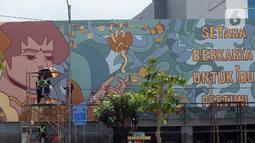 """Suasana saat para muralis perempuan menyelesaikan pembuatan mural pada dinding di kawasan Juanda, Jakarta, Rabu (16/6/2021). Mural tersebut berjudul """"Setara Berkarya untuk Ibu Pertiwi"""". (merdeka.com/Imam Buhori)"""