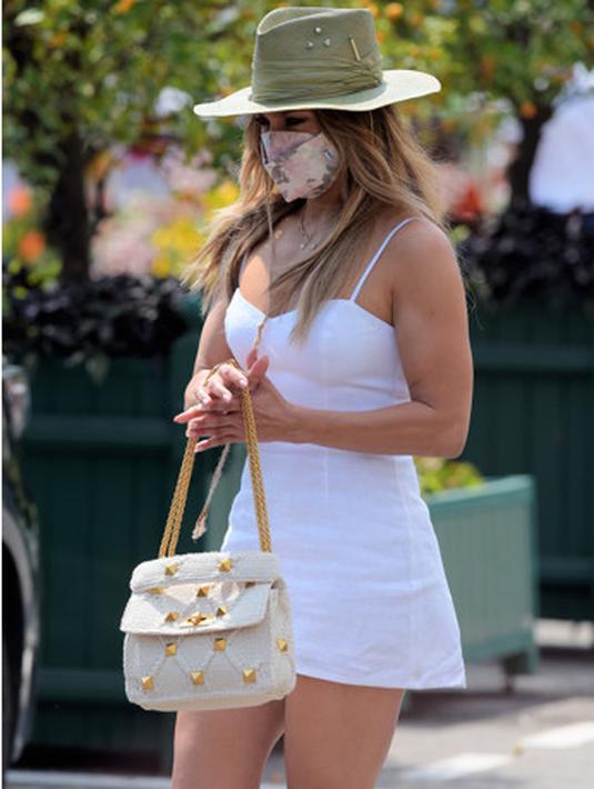 Saat berada di Montercarlo, Jennifer Lopez terlihat mengenakan spaghetti mini dress dipadukan dengan topi koboy dan handbag dari koleksi Valentino Garavani Roman Stud bag. CREDIT: Valentino