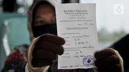 Salah seorang penumpang menunjukkan surat keterangan sehat di Terminal Pulo Gebang, Jakarta, Minggu (17/5/2020).  Saat ini tercatat hanya ada 38 PO bus yang masih beroperasi dengan batas maksimal mengangkut penumpang mulai 6-10 orang dalam 1 bus. (merdeka.com/Iqbal S. Nugroho)