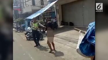Seorang polisi amankan senjata tajam dari wanita tanpa busana yang diduga alami gangguan jiwa.