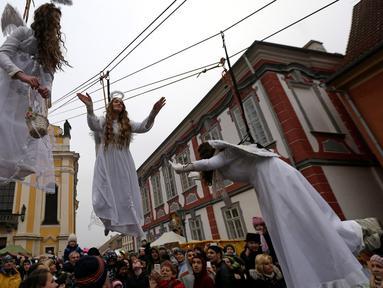 Sejumlah wanita berpakaian seperti malaikat berayunan diatas ratusan penonton saat acara pasar Natal di kota Ustek, Republik Ceko (17/12). Mereka melakukan aksi ini dalam rangka untuk menyambut datangnya natal. (Reuters/David W Cerny)